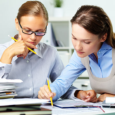 Image of two business women reading over notes